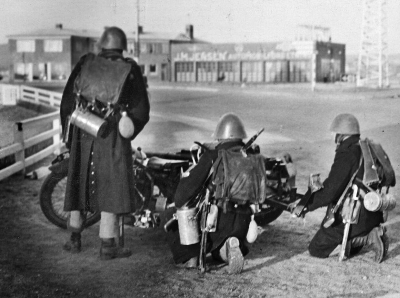 Tyske tropper rykker frem gennem Aabenraa om morgenen d. 9. april 1940. En dansk maskinkanon-gruppe er klar til at yde modstand mod tyskerne fremrykning.; A Danish cannon group tries to resist the German forces driving through Aabenraa in the morning on 9th April, 1940.;