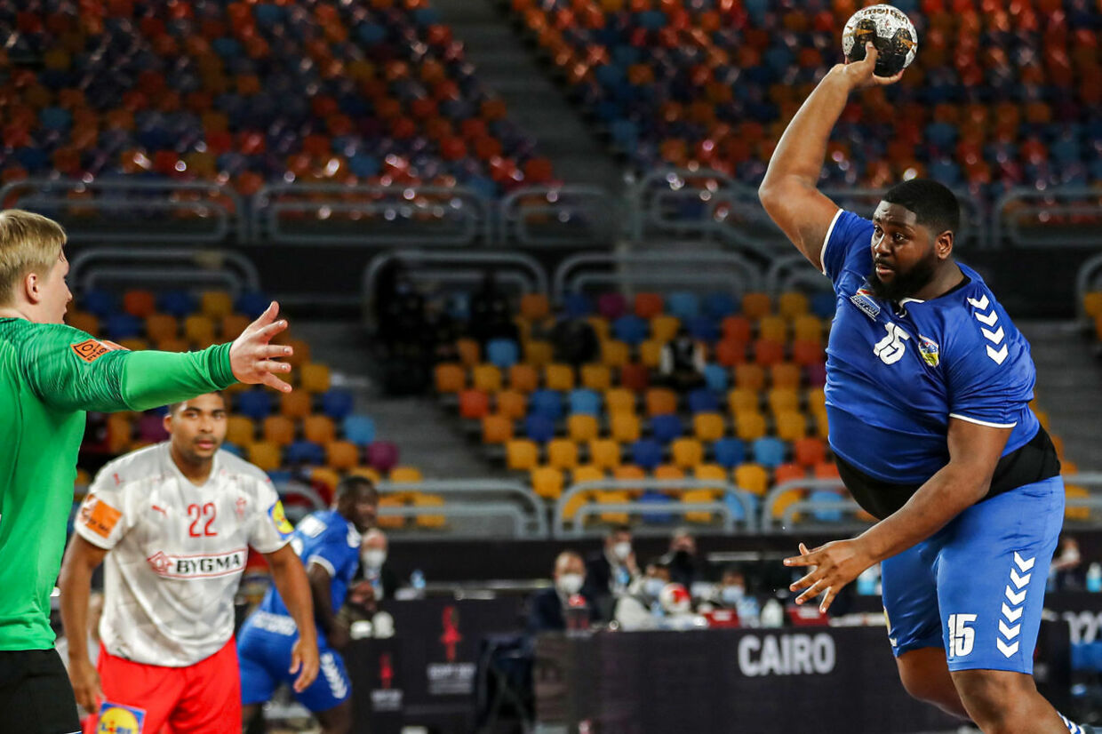 Democratic Republic of Congo's pivot Gauthier Mvumbi (R) attempts a shot during the 2021 World Men's Handball Championship match between Group D teams DR Congo and Denmark at the Cairo Stadium Sports Hall in the Egyptian capital on January 17, 2021. (Photo by MOHAMED ABD EL GHANY / POOL / AFP)