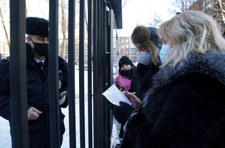 Aleksej Navalnys advokater måtte mandag forhandle gennem jerngitteret til politistationen i Khimki uden for Moskva, hvor oppositionspolitikeren bliver tilbageholdt efter sin anholdelse søndag.