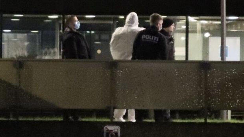 Her bliver den anholdte fulgt væk i en hvid kedeldragt