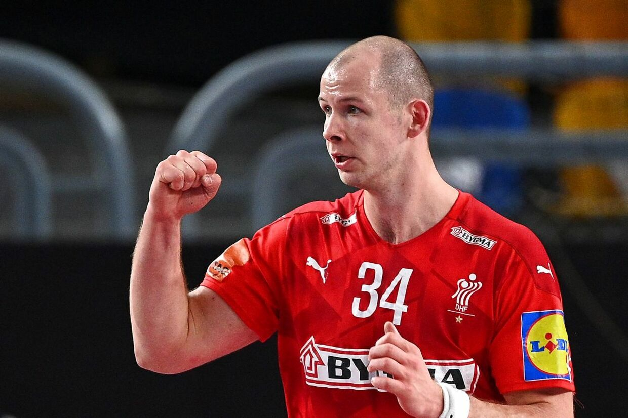 Denmark's pivot Simon Hald Jensen celebrates after scoring during the 2021 World Men's Handball Championship between Group II teams Denmark and Qatar at the Cairo Stadium Sports Hall in the Egyptian capital on January 21, 2021. (Photo by Anne-Christine POUJOULAT / POOL / AFP)