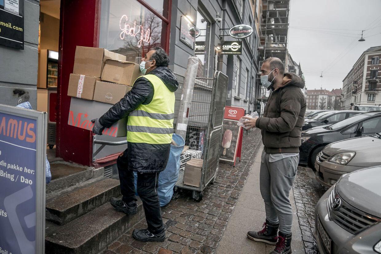 Her står folk i kø til en pakkeshop med mundbind på. Måske kan det snart blive et krav med mundbind i det offentlige rum.