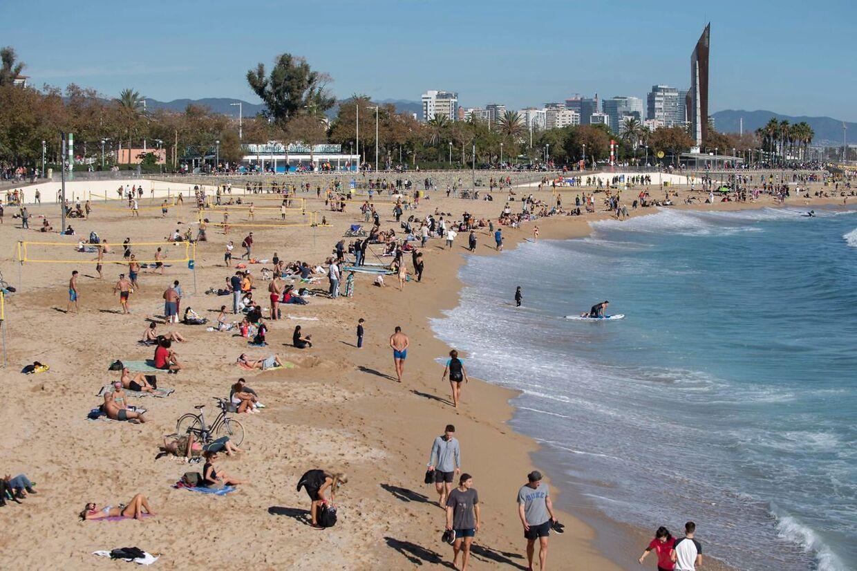 Folk tager solbad på stranden ved Barcelona.