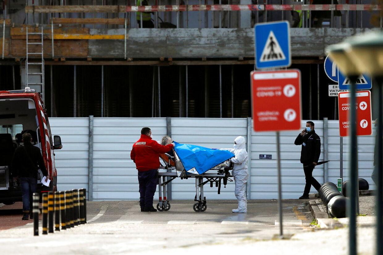 Man kører patienter ind på hospitalet fra ambulancer på gaden i Lisabon.
