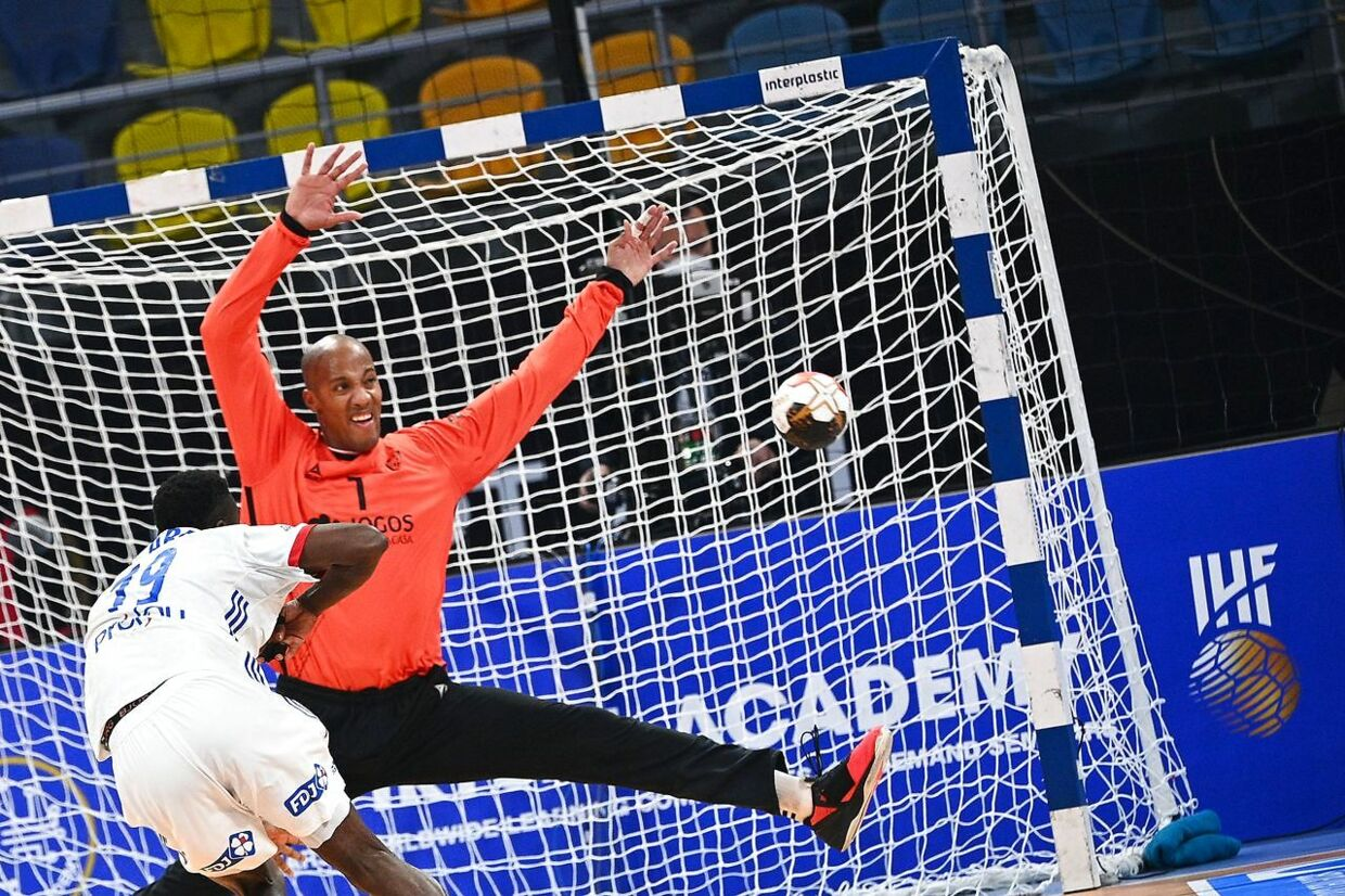 Portugal's goalkeeper Alfredo Quintana (back) fails to stop a ball during the 2021 World Men's Handball Championship match between Group III teams Portugal and France at the 6th of October Sports Hall in 6th of October city, a suburb of the Egyptian capital Cairo on January 24, 2021. (Photo by Anne-Christine POUJOULAT / POOL / AFP)