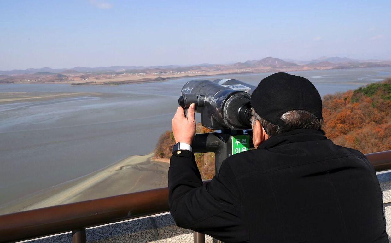 En mand ser på Nordkorea gennem kikkerten fra Sydkorea.