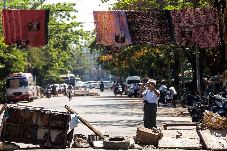 En mand fotograferer en barrikade lavet af longyier.
