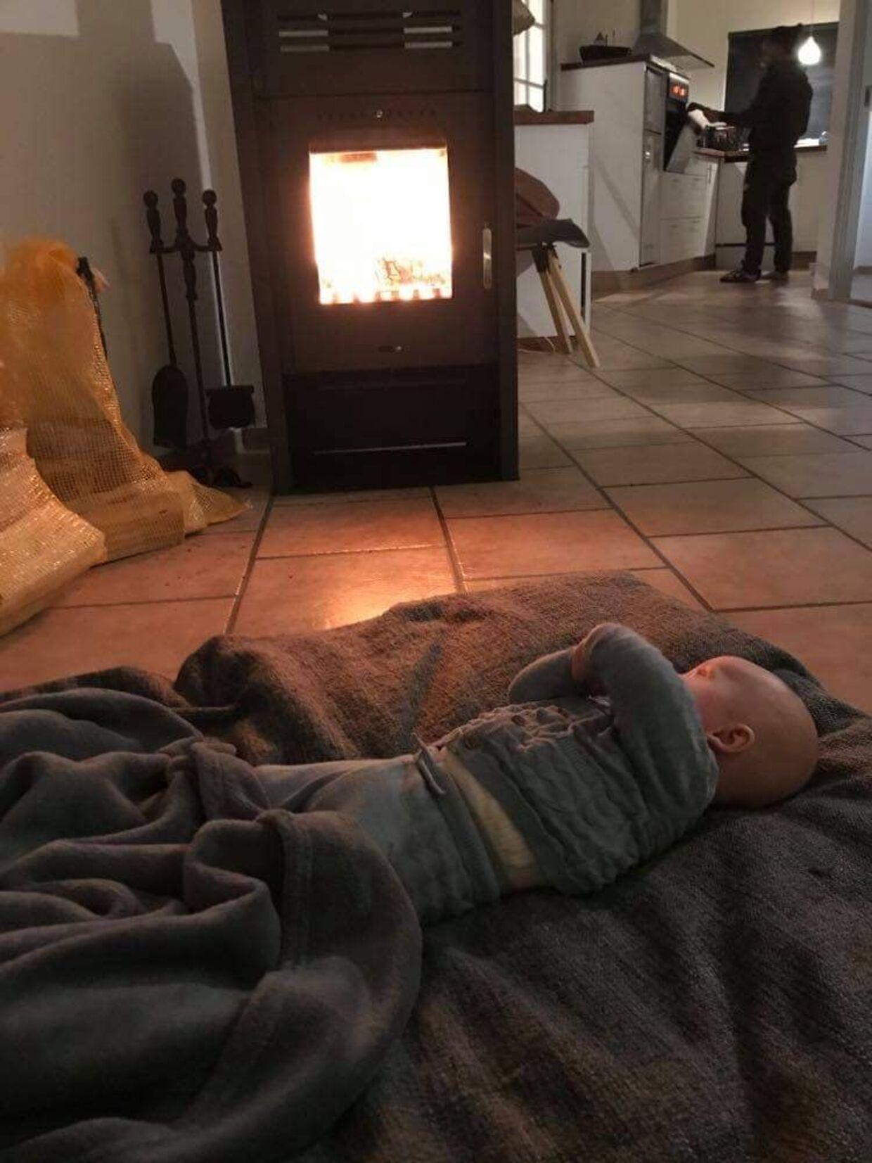 Mathias og Stines baby ligger foran brændeovnen. Det eneste sted, hvor der var bare nogenlunde varmt i sommerhuset.