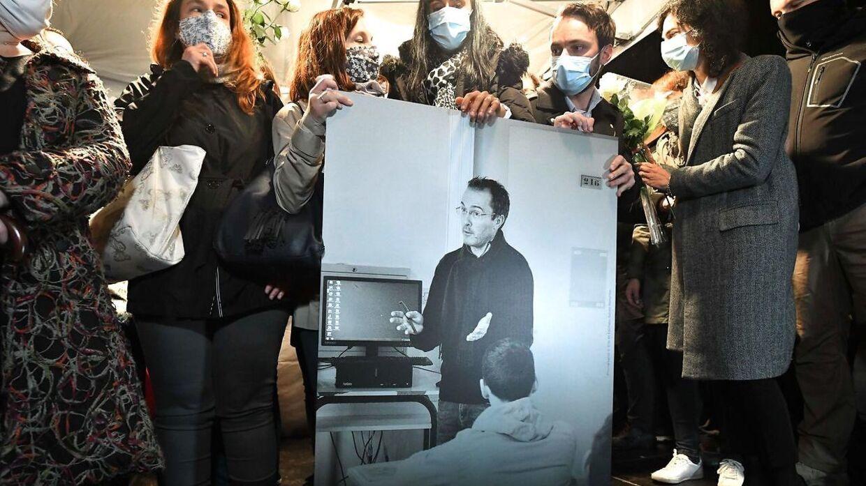 Samuel Patys kolleger og pårørende holder et billede af ham under en mindehøjtidelighed i oktober 2020. Nu viser det sig, at den fortælling, der startede kædereaktionen, der første op til hans død, bygger på en løgn. (Arkivfoto)
