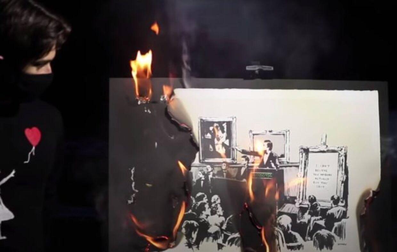 Her brændes Banksy-billedet, der meget passende hedder Morons (paphoveder/spader/glatnakker/idioter). Siden blev en digital version solgt for cirka tre millioner kroner.