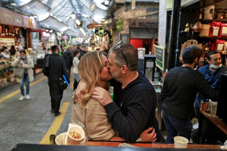 Et par kysser på et marked i Jerusalem i marts 2021. (Photo by MENAHEM KAHANA / AFP)