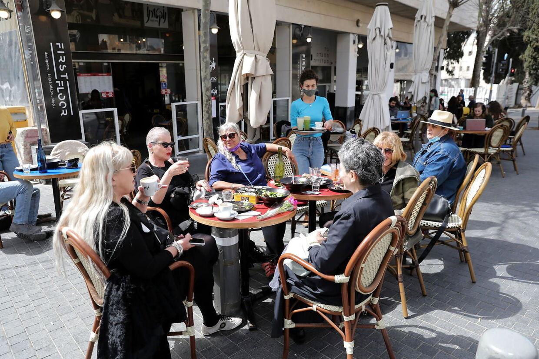 Israelerne kan igen samles på restauranter, cafeer og barer i takt med, at smittetallene er raslet ned. EPA/ABIR SULTAN