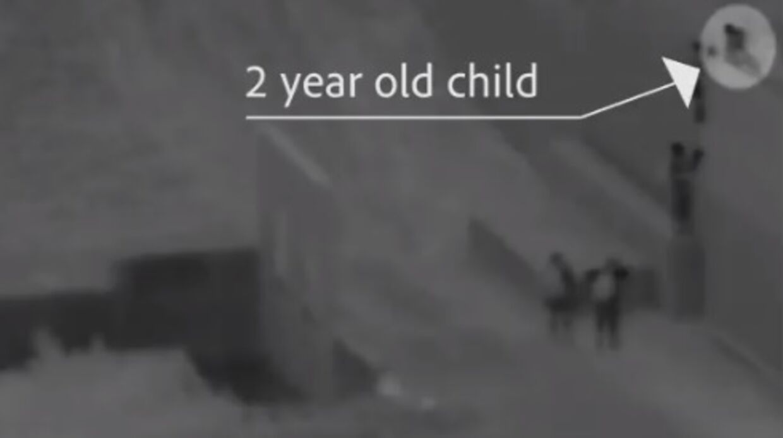 Her ses det lille barn på vej over grænsemuren.