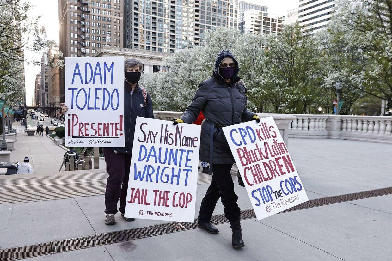 Kvinder bærer skilte, som protesterer mod drabet på den 13-årige Adam Toledo i Chicago.
