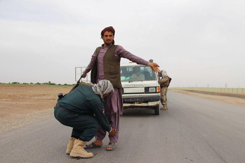 Afghanske sikkerhedsstyrker tjekker folk ved et checkpoint i Helmand-provinsen i april 2021. EPA/WATAN YAR