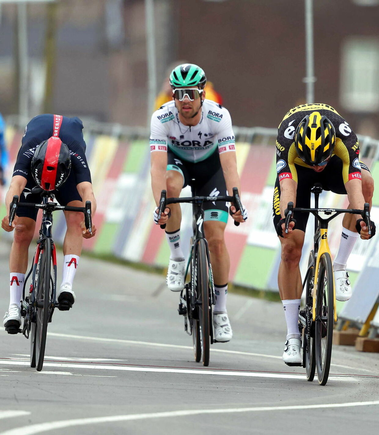 epa09143724 Belgian rider Wout Van Aert (R) of Team Jumbo-Visma crosses the finish line to win the Amstel Gold Race over 218.6km in Valkenburg, Netherlands, 18 April 2021. Van Aert won ahead of second placed British rider Thomas Pidcock (L) of the Ineos Grenadiers team and third placed German rider Maximilian Schachmann (C) of the Bora - Hansgrohe team. EPA/Marcel Van Hoorn