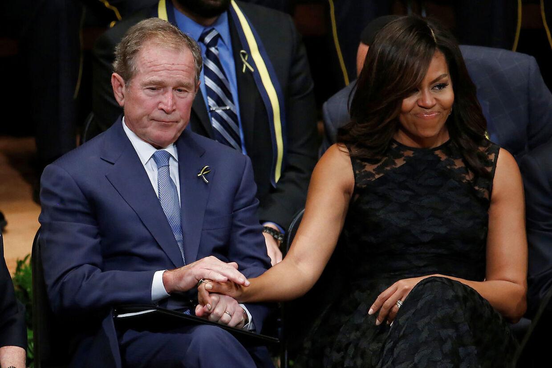 George W. Bush og Michelle Obama holder hånd under en mindeceremoni.