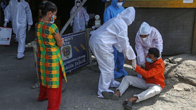 Sundhedsarbejdere tilser en coronaramt mand i Mumbai. Indien har oplevet en eksplosiv vækst i antallet af nye tilfælde.