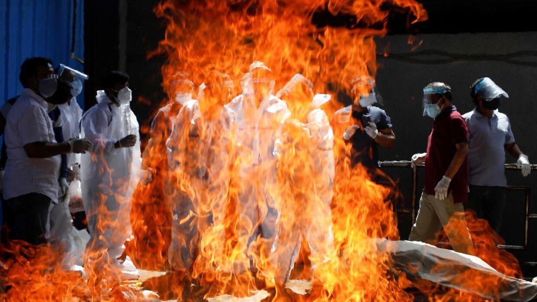 Pårørende iført fuld beskyttelse til en rituel begravelse for en mand, der er død af coronavirus, i millionbyen New Delhi.