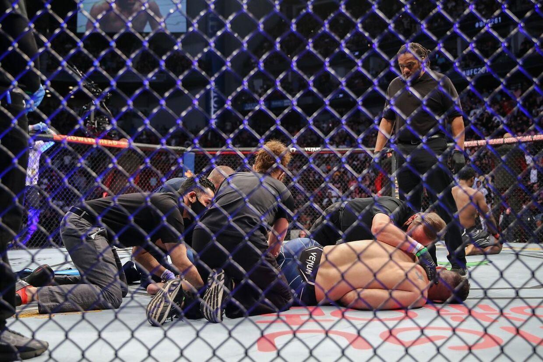 Chris Weidman måtte beroliges af læger efter chokskaden. I baggrunden til højre ses Uriah Hall, som heller ikke kunne holde til at se på de horrible scener.