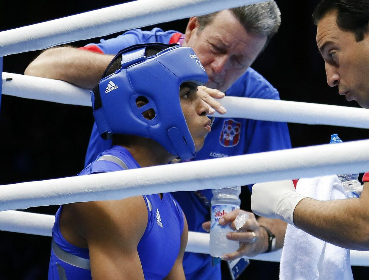 Felix Verdejo Sanchez of Puerto Rico listens to his corner between rounds against Ahmed Mejri of Tunisia during their Lightweight (60kg) match of the London 2012 Olympic Games at the ExCel Arena on August 2, 2012 in London. Verdejo Sanchez was awarded a 16-7 points decision. AFP PHOTO / Jack GUEZ. JACK GUEZ / AFP