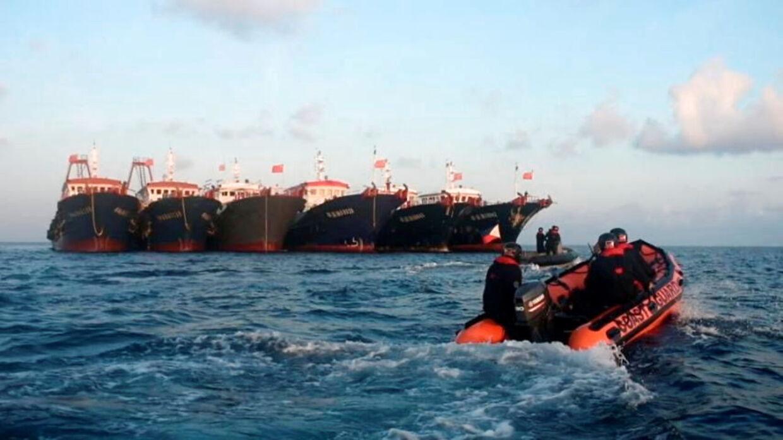 En lille både fra den filippinske kystvagt ses foran nogle af de kinesiske fartøjer.