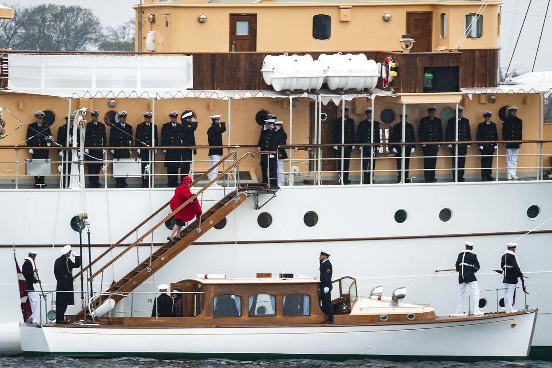 Her går en dronning Margrethe klædt i rødt officielt ombord på Kongeskibet Dannebrog i Københavns Havn.