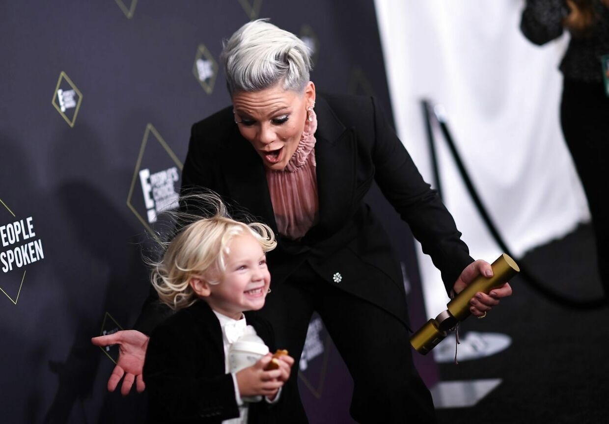 (FILES) In this file photo US singer/songwriter Pink reacts as her son Jameson Moon Hart runs towards her as she gets ready to pose with the People's Champion Award during the 45th annual E! People's Choice Awards at Barker Hangar in Santa Monica, California, on November 10, 2019. - On April 3, singer Pink announced on twitter that she and her son showed symptoms of Covid-19 2 weeks ago. She tested positive. They both were re-tested and are now negative. She donated half a million dollars to Temple University Hospital Emergency Hospital in Philadelphia (where her mom worked for 18 years) and another half million to the City Of Los Angeles Maypr's Emergency Covid-19 Crisis Fund. (Photo by VALERIE MACON / AFP)