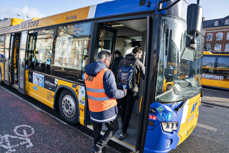 Guider fra Nordjyllands Trafikselskab deler løbesedler ud med advarsler om smittefare i overfyldte busser ved busterminalen i Aalborg, 11. marts 2020.. (Foto: Henning Bagger/Ritzau Scanpix)