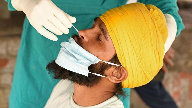En mand får taget en prøve fra næsen, som skal vise om han er smittet med covid-19.