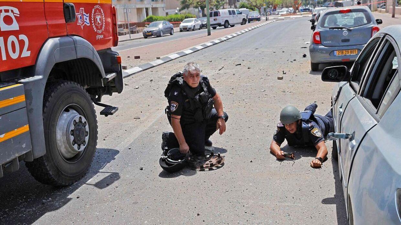 Israelske sikkerhedsstyrker søger dækning, da raketter sendt fra Gazastriben rammer i den sydlige israelske by Ashkelon. Billedet her er fra 11. maj.