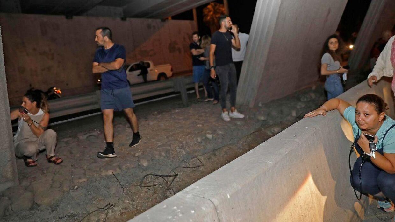 Folk søger dækning under en bro i den israelske by Tel Aviv efter raketter er blevet affyret fra Gaza. Billedet er fra den 11. maj.