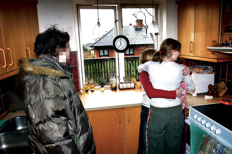 De to søskende flygtede fra deres mor (tv.) for at bo hos deres storesøster, som holder om dem i køkkenet (th.) Fotoet blev taget den dag, hvor moren, mormoren og en sagsbehandler fra kommunen kom for at tvinge pigerne tilbage til Ærø. Det lykkedes dog ikke på grund af børnenes skrig og modstand. Mandag 12. januar 2004.