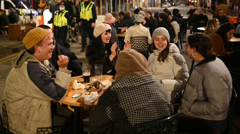 En gruppe unge nyder en øl på en bar i England, hvor vaccineudrulningen er gået en del strærkere end i Danmark.