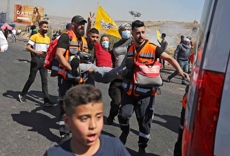 Palastinænsere bærer en såret mand væk fra gaden i Ramallah.