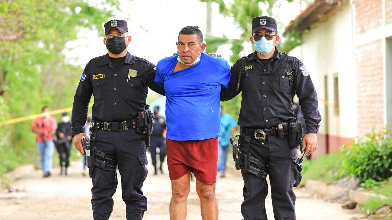 Den tidligere politimand Hugo Ernesto Osorio i politiets vartægt. (Photo by - / NATIONAL CIVIL POLICE / AFP)
