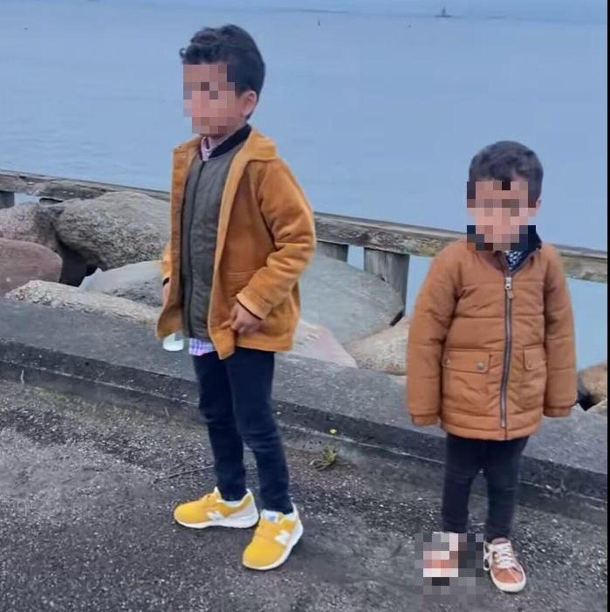 Seksårige Iyad og treårige Malek så på, mens deres forældre diskuterede med den fremmede mand på havnen.