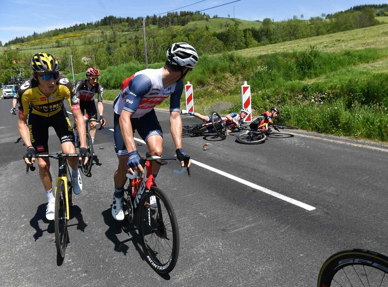 Team Bahrain's Santiago Buitrago of Colombia (R) and Team Trek's Mads Pedersen of Denmark are watched by other riders after crashing during the third stage of the 73rd edition of the Criterium du Dauphine cycling race, 172km between Langeac and Saint-Haon-Le-Vieux on June 1, 2021. (Photo by Alain JOCARD / AFP)