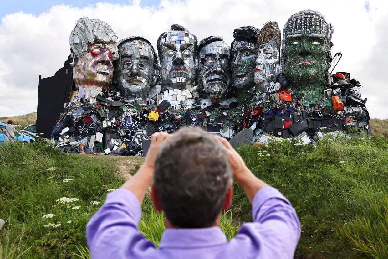 En mand fotograferer 'Mount Recyclemore' ved byen St. Ives. Portrætterne af de syv ledere af G7-landene er lavet af elektronisk affald af kunstneren Joe Rush.
