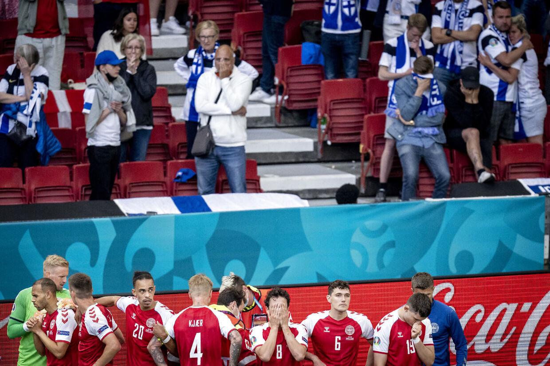 Danmarks Christian Eriksen får behandling imens at danske spillere skærmer for ham og mens fans ser til i baggrunden under kampen mellem Danmark og Finland i gruppe B under EURO2020 i Parken i København, lørdag den 12. juni 2021.. (Foto: Mads Claus Rasmussen/Ritzau Scanpix)