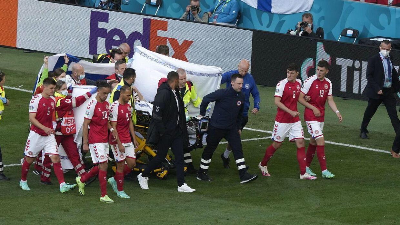 Christian Eriksen blev fragtet ud af Parken omringet af sine holdkammerater.