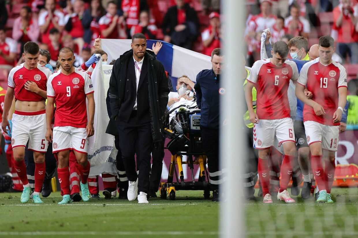 TOPSHOT - Denmark's players escort Denmark's midfielder Christian Eriksen (C) as he is evacuated after collapsing on the pitch during the UEFA EURO 2020 Group B football match between Denmark and Finland at the Parken Stadium in Copenhagen on June 12, 2021. (Photo by Friedemann Vogel / various sources / AFP)