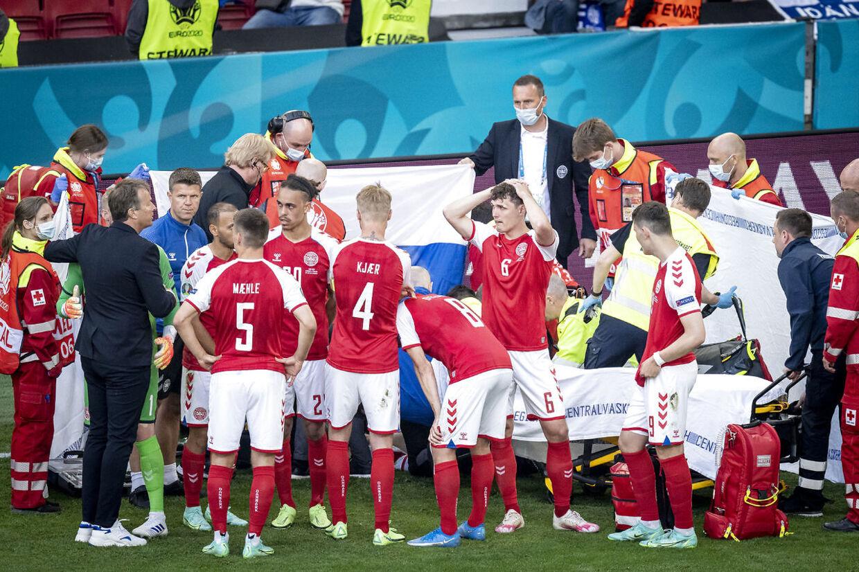 Redningsfolk og spillere står tæt om Christian Eriksen, kort efter han bliver ført ud af Parken og ud mod Rigshospitalet.