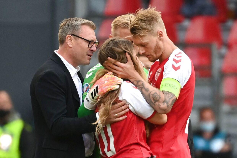 Simon Kjær og Kasper Schmeichel tager sig af Christian Eriksens kæreste, Sabrina Kvist Jensen, da hun løber ind på banen.