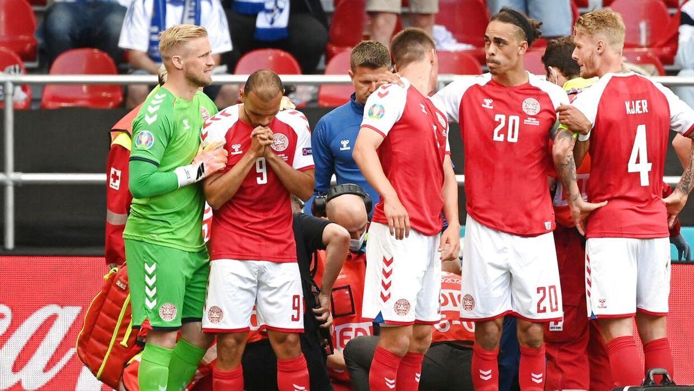 De danske landsholdsspillere danner en menneskering om Christian Eriksen, der modtager behandling.