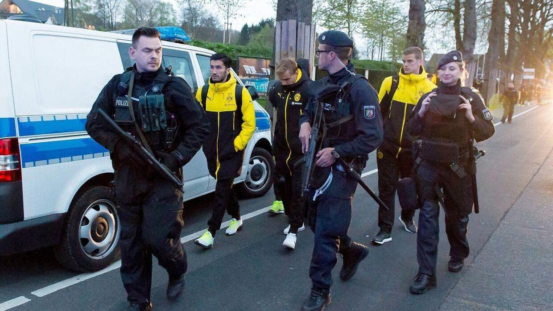 Chokerede Dortmundspillere med politieskorte 11. april 2017 efter tre bomber havde ramt deres spillerbus på vej til stadion.