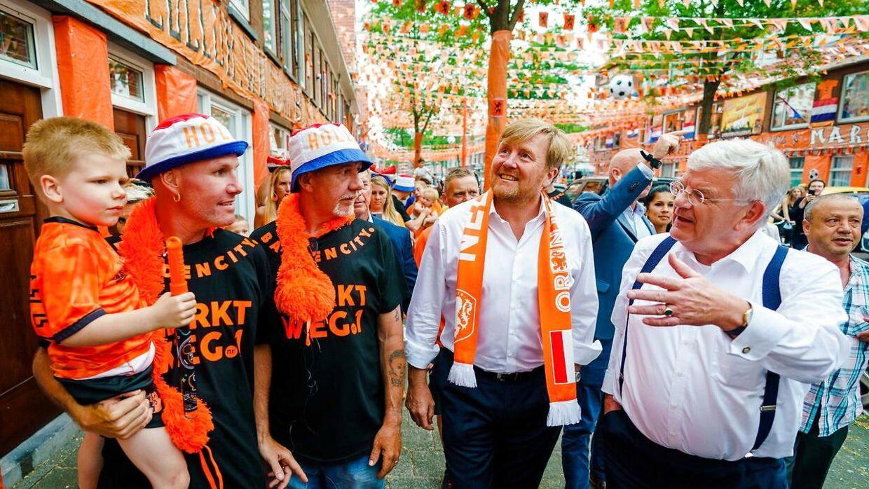 Den hollandske kong Willem-Alexander og Haags borgmester Jan van Zanen hilser på nogle beboere på Marktweg i Haag, netop kåret til Hollands smukkeste orange by.