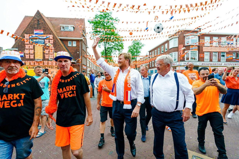 Den hollandske kong Willem-Alexander havde iført sig sit landsholdstørklæde, da han kom på uanmeldt besøg og overraskede beboerne på Marktweg-gaden i Haag.