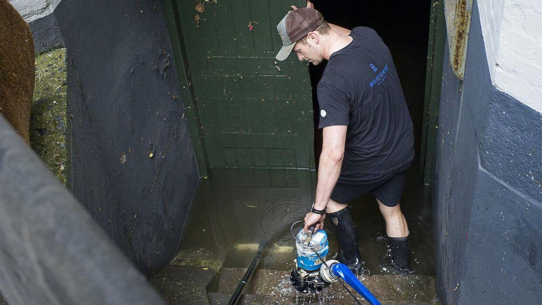 (ARKIV) Vand pumpes op fra en kælder i Store Kongensgade efter et skybrud.