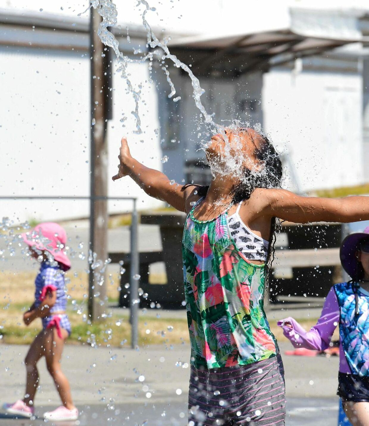 Kids cool off at a community water park on a scorching hot day in Richmond, British Columbia, June 29, 2021.